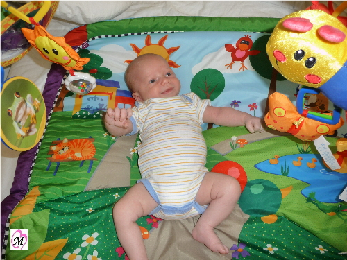 Infant playing on play mat