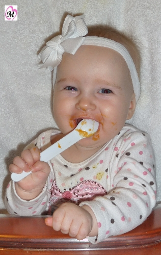 Baby feeding self with spoon